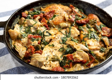 Homemade Creamy Tuscan Chicken in a cast iron pan, side view. Close-up.