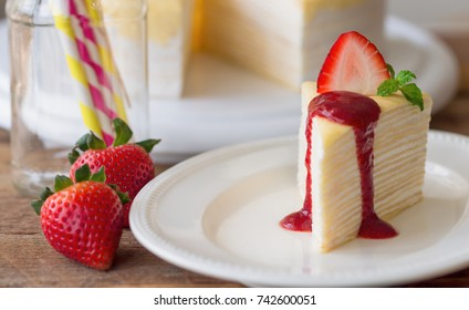 Homemade crepe cake and strawberries sauce decorate by mint and fresh strawberry so delicious soft sweet and sour for birthday party or coffee break. Crepe cake or mille crepe is French dessert.