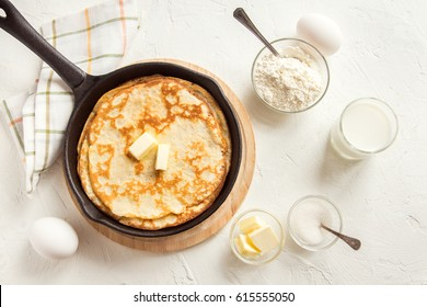 Homemade crepes with butter in cast iron pan and ingredients over rustic white background - cooking fresh homemade breakfast crepes pancakes food