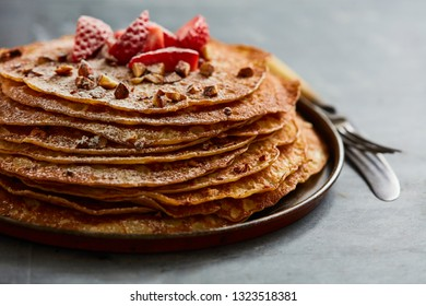 Homemade crepes with castor sugar, roast almonds and fresh strawberries