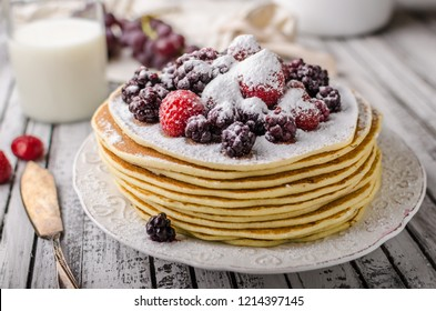 Homemade crepes with frozen berries, topped sugar, rustic wood board, vintage photography