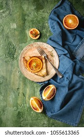 Homemade crepes pancakes served in ceramic plate with bloody oranges and rosemary syrup with sliced sicilian red oranges and blue cloth over green texture background. Top view, space