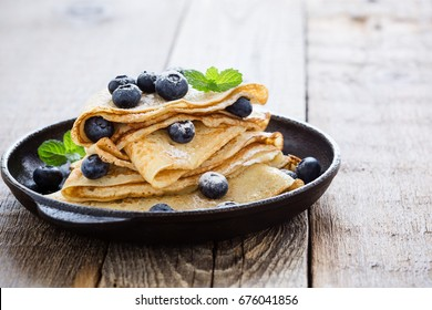 Homemade  crepes served with fresh blueberries and powdered sugar on rustic wooden table in cast iron skillet