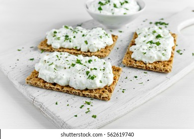 Homemade Crispbread toast with Cottage Cheese and parsley on white wooden board