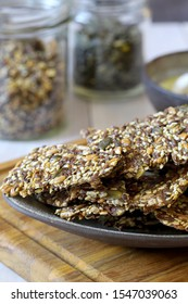Homemade crispy gluten free flatbread cracker with lots of seeds and psyllium on white background. Healthy snack, seed crackers - horizontal image