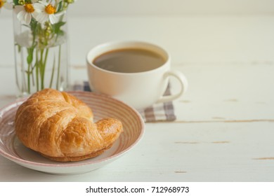 Homemade croissant on plate served with black coffee or americano. Delicious and quick breakfast with fresh croissant and coffee. Croissant and black coffee for breakfast on wood table with copy space