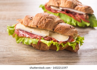 Homemade croissant sandwich with meat, cheese and fresh lettuce on a wooden background.