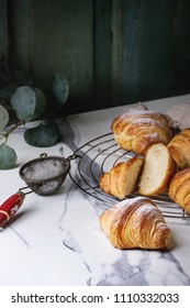 Homemade croissant whole and sliced with sugar powder on cooling rack. Decorated by eucalyptus branch over white marble table.