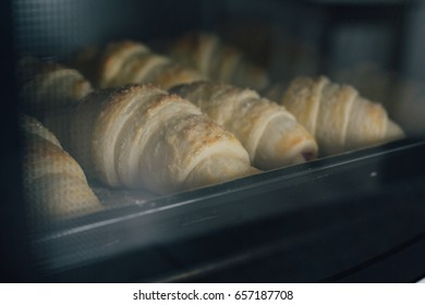 Homemade croissants are baked in the oven. Selective focus. Toning.