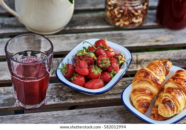 Homemade croissants, fresh berries,  and  juice for breakfast on dark wooden background. Health and diet concept.