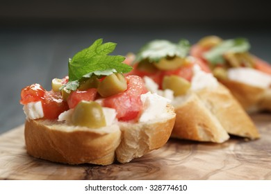 homemade crostini with tomato, mozzarella and olives on wooden table