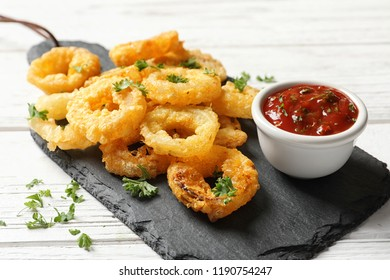 Homemade crunchy fried onion rings with tomato sauce on wooden table, closeup