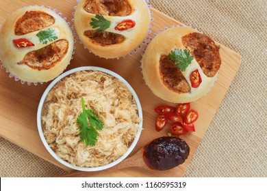 Homemade cup of soft and sticky bun with dried shredded pork or pork floss and shrimp roasted chili paste on wood table in top view flat lay. Thai style delicious bread with sweet and spicy taste.