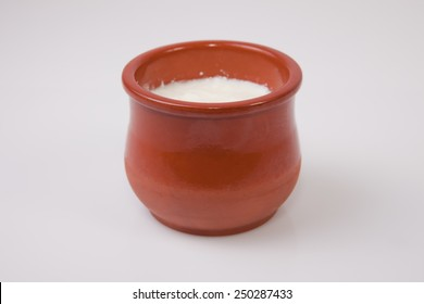 Homemade curd in clay pot made from cow milk. Isolated over white background