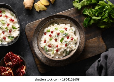 Homemade Curd Rice with pomegranate, cilantro, ginger on a black background. Top view. Traditional Indian South cuisine
