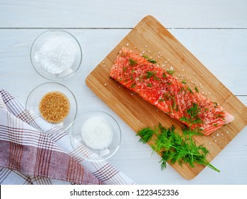 Homemade cured salmon gravlax. Raw salmon prepared for dry cure with salt, sugar and dill over wooden board, overhead top view.