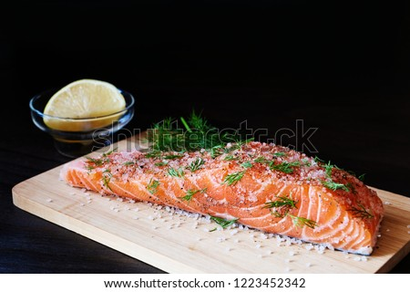 Homemade cured salmon gravlax. Raw salmon prepared for dry cure with salt, sugar and dill over wooden board on dark background.