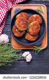 Homemade cutlets with herb and spices  on  black wooden background. Selective focus. Vertical image.