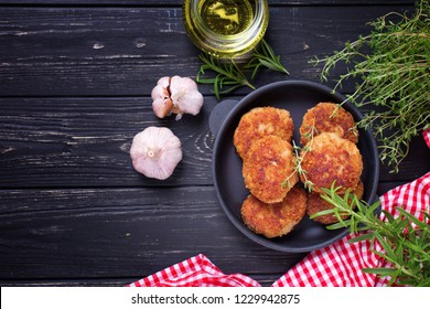 Homemade cutlets with herb and spices  on  black wooden background. Selective focus. Place for text. Top view.