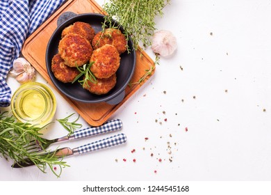 Homemade cutlets and herb and spices on frying pan  on wooden board on light textured background. Selective focus.