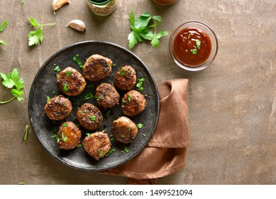 Homemade cutlets from minced meat on plate over brown background. Top view, flat lay