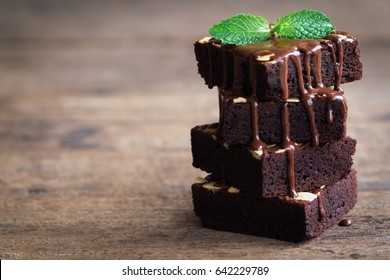 Homemade dark chocolate brownies topping with almond slices and mint stacked on wood table with copy space. Delicious bitter sweet and fudge. Brownie is one type of chocolate cake.