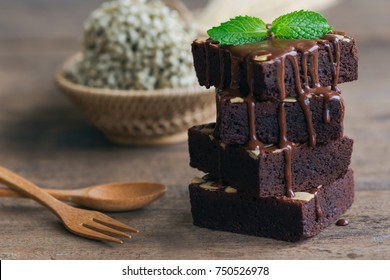 Homemade dark chocolate brownies topping with almond slices and mint stacked on wood table with copy space. Delicious bitter sweet and fudge. Brownie is one type of chocolate cake. Vintage tones.