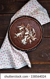 homemade dark chocolate tart  on rustic background