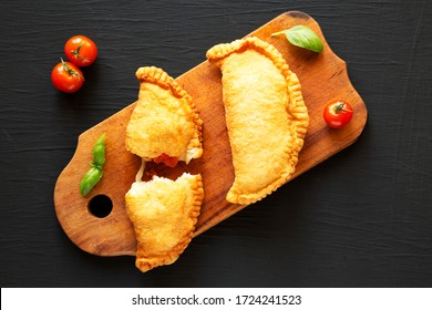 Homemade Deep Fried Italian Panzerotti Calzone with tomato and mozzarella on a rustic wooden board on a black background, top view. Flat lay, overhead, from above.