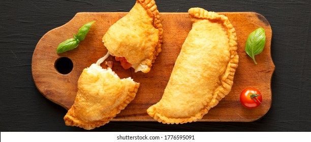 Homemade Deep Fried Italian Panzerotti Calzone with tomato and mozzarella on a rustic wooden board on a black surface, top view. Flat lay, overhead, from above.