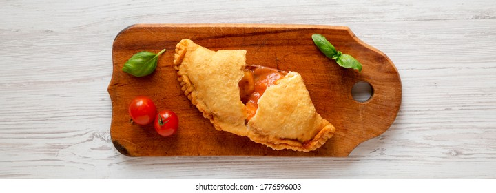 Homemade Deep Fried Italian Panzerotti Calzone with sauce on a rustic wooden board, overhead view. Flat lay, top view, from above.