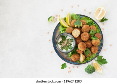 Homemade deep-fried vegetarian  falafel made from ground chickpeas and broccoli,  are laid over a bed of salads .  Middle Eastern food.