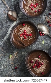 Homemade delicate chocolate mousse with cranberries and chocolate chips in serving ceramic bowls on a gray stone background. Top View