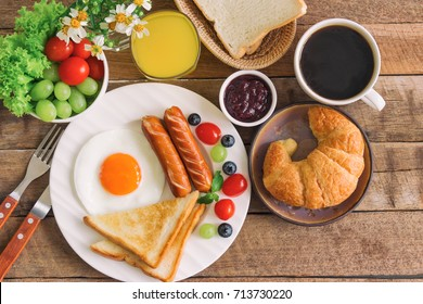 Homemade delicious american breakfast with sunny side up fried egg, toast, sausage, fruits, vegetable, strawberry jam, croissant, black coffee and fresh orange juice in top view flat lay style.