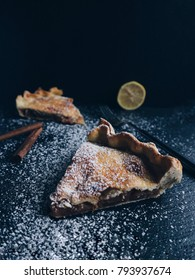 Homemade delicious apple pie on a white plate and black stone background. Cinnamon sticks, citrus, sugar powder. Space for text.