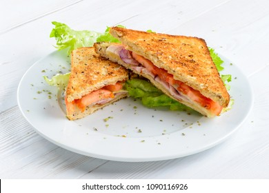 Homemade delicious BLT sandwiches with bacon, fresh lettuce and tomatoes on the plate on white rustic background. Tasty breakfast or lunch