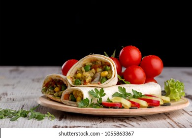 Homemade delicious burrito with vegetables on a wooden background
