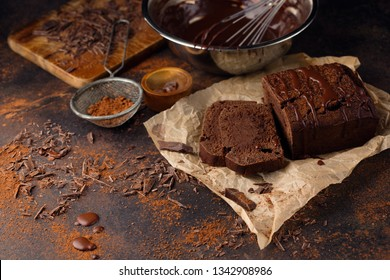 Homemade delicious chocolate cake and sauce in bowl with whisk on dark wooden table, selective focus