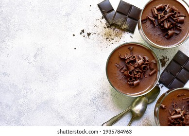 Homemade delicious chocolate mousse or panna cotta  in a glasses on a light slate, stone or concrete background. Top view with copy space.