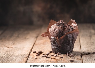 Homemade delicious chocolate muffin on wooden background close-up