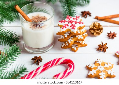 Homemade delicious Christmas gingerbread cookies with glass of milk on the white wooden background