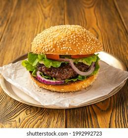 Bel hamburger fait maison sur une table en bois, style rustique. Restauration rapide. Espace pour le texte.