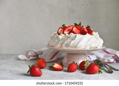 "Homemade delicious meringue cake ""Pavlova"" with fresh straberry and mascarpone on a white background."