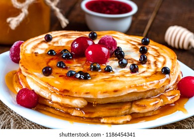 Homemade, delicious pancakes with fresh berries and honey on a wooden background. Delicious, healthy breakfast. Pancakes with honey. Pancakes with maple syrup