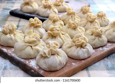 Homemade delicious raw manti (turkish ravioli) from dough on a board sprinkled with flour. Preparation of Manti. Manti, Mantu or Manty Momos, Jiaozi, Dyushbara, Sikkim, Darjeeling,  Mandu, Manti, Pier