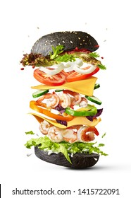Homemade delicious sandwich of flying ingredients shrimp, fresh organic vegetables and black bun on a white background with copy space.