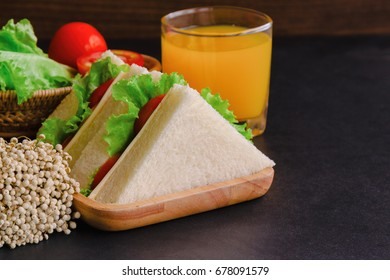 Homemade delicious sandwich ham cheese with lettuce and tomato in triangle shape on wood plate served with fresh orange juice on granite table with copy space for breakfast.