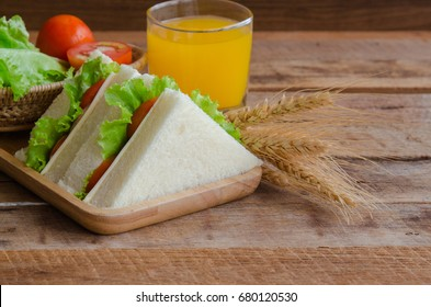 Homemade delicious sandwich ham cheese with lettuce and tomato in triangle shape on wood plate served with fresh orange juice on wooden table with copy space for breakfast.