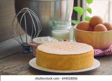 Homemade delicious sponge cake or soft cake on white plate with ingredients: eggs flour milk put on wood table with copy space near windows. Bakery concept for background or wallpaper.