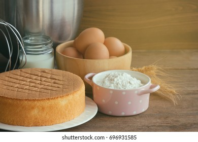 Homemade delicious sponge cake or soft cake on white plate with ingredients: eggs flour milk put on wood table with copy space under sunlight. Bakery concept for background or wallpaper.